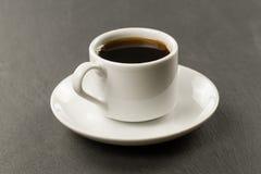 Biała filiżanka kawy na czarnym tle Fotografia Stock