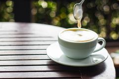 Biała filiżanka kawy umieszcza na brown drewnianym stole i Obraz Royalty Free