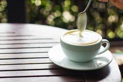 Biała filiżanka kawy umieszcza na brown drewnianym stole i Zdjęcia Stock