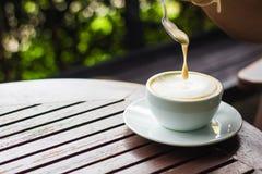 Biała filiżanka kawy umieszcza na brown drewnianym stole i Zdjęcie Stock