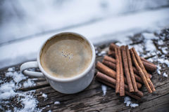 Biała filiżanka kawy z piankowymi cynamonowymi kijami na śnieżnych płatków wi, Obrazy Royalty Free