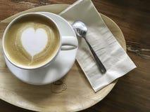 Biała filiżanka kierowa kształta cappuccino kawa na drewno talerzu Fotografia Stock