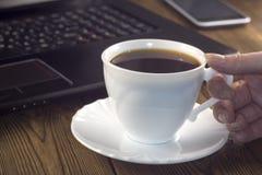 Biała filiżanka laptopu telefonu ręka na drewnianej tło kawie, fotografia royalty free