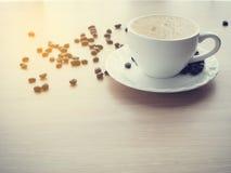 Biała filiżanka latte kawa i kawowa fasola, grże brzmienie Zdjęcia Royalty Free