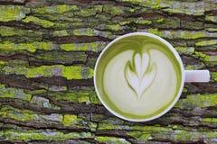 Biała filiżanka matcha zielonej herbaty latte sztuka z pianą na nieociosanego mech drewnianym stole z kopii przestrzenią fotografia stock