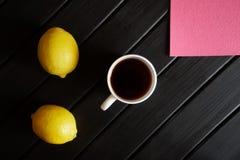 Biała filiżanka z czarnej herbaty stojakami na czarnym stole obok dwa żółtych cytryn i różowej pieluchy na widok minimalista zdjęcie stock