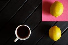 Biała filiżanka z czarnej herbaty stojakami na czarnym stole obok różowej pieluchy i dwa żółtych cytryn na widok minimalista zdjęcie stock