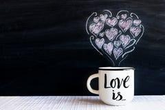 Biała filiżanka z ręki literowania teksta miłością JEST i rysujący mały Fotografia Stock