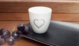 Biała filiżanka z sercem na drewnianym stole Obrazy Stock