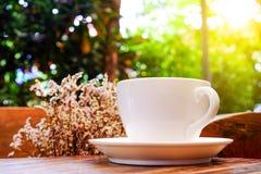 Biała filiżanka z suchym kwiatem na drewnianym stole Ostrości kawy wi zdjęcia stock