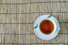 Biała filiżanki herbata na drewnianej macie od odgórnego widoku Zdjęcia Royalty Free