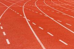 Biała junakowanie linia na czerwonym bieg śladzie Obraz Stock