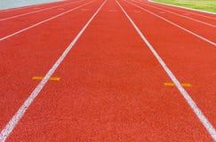 Biała junakowanie linia na czerwonym bieg śladzie Zdjęcia Stock