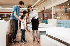 Biała kobieta konsultant demonstruje ortopedyczną materac potomstwa ojcuje z dziećmi w meblarskim sklepie fotografia stock