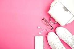 Biała kobieta modnisia akcesoria plecak, sneakers, telefon i eyeglasses mieszkanie z hełmofonami, kłaść na różowym tle z teksta z Fotografia Stock