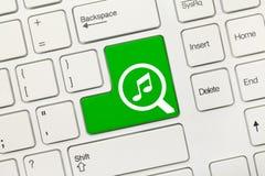 Biała konceptualna klawiatura - Szuka zielonego klucz z loupe i muzycznymi symbolami fotografia royalty free
