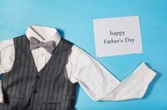 Biała koszula, szarość przekazuje i łęku krawat na jaskrawym błękitnym tle Fotografia Stock
