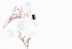 Biała kremowa butelka umieszczał i kwiaty, Pusty etykietka pakunek dla egzaminu próbnego up na białym tle Pojęcie naturalny piękn Obraz Stock