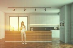 Biała kuchnia z drewnianą wyspą, kobieta ilustracji