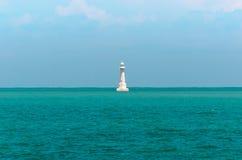 Biała latarnia morska po środku morza Zdjęcia Stock