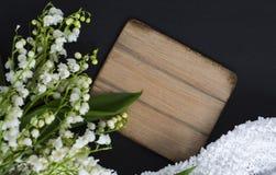 Biała leluja dolina kwiaty na czarnym tle z drewnianą deską kopiować astronautyczną i delikatną tkaninę zdjęcia royalty free