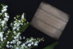 Biała leluja dolina kwitnie na czarnym tle z drewnianą deską dla kopii przestrzeni obrazy stock