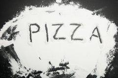 Biała mąka na czarnym stole, wpisowa pizza obrazy stock