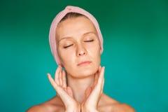 Biała młoda kobieta stawia dalej twarzy maskę na turkusowym tle w domu Europejska kobieta myje jej twarz z wodą zamkniętą w górę  zdjęcie stock