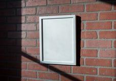 Biała obrazek rama na Czerwony ściana z cegieł portreta Odległym Wędkującym Zdjęcia Royalty Free