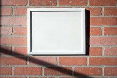 Biała obrazek rama na Czerwonym ściana z cegieł krajobrazie Obraz Stock