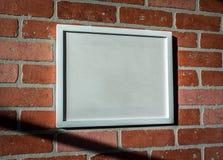 Biała obrazek rama na Czerwonym ściana z cegieł krajobrazie Wędkującym Obraz Stock