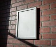 Biała obrazek rama na Czerwonym ściana z cegieł portrecie Wędkującym Obraz Stock