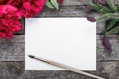 Biała papierowa karta z muśnięciem na nieociosanym drewnianym tle z różowymi peoniami, płatkami i świerczyną, rozgałęzia się z ro Zdjęcia Royalty Free