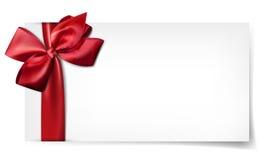 Biała papierowa karta z prezenta czerwonym atłasowym łękiem. Zdjęcia Stock