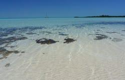 Biała piasek plaża z żaglówką zdjęcia stock