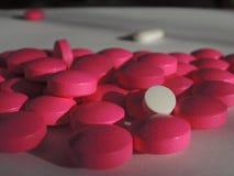 Biała pigułka wśród różowych pigułek: rozsypisko leki Zdjęcia Royalty Free