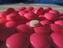 Biała pigułka wśród różowych pigułek: rozsypisko leki Obraz Stock