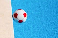 Biała plażowa piłka unosi się w pływackim basenie Zdjęcia Royalty Free