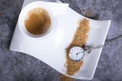 Biała porcelany filiżanka z brązu cukierem i kieszeniowym zegarkiem obraz stock