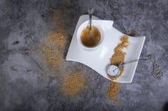 Biała porcelany filiżanka z brązu cukierem i kieszeniowym zegarkiem zdjęcia stock