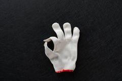 Biała rękawiczka z gestem OK na czerni obrazy stock