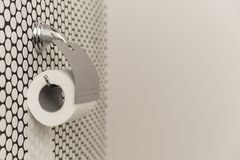 Biała rolka starannie wiesza na nowożytnym chromu właścicielu na lekkiej łazienki ścianie miękki papier toaletowy Obrazy Stock