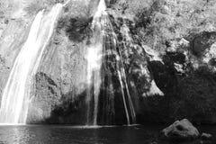 Biała siklawa ono ślizga się na skałach czarny i biały zdjęcie stock