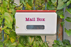 Biała skrzynka pocztowa przy ogrodzeniem Fotografia Royalty Free