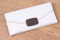 Biała sprzęgłowa torba na z drewnianym tłem Obraz Royalty Free