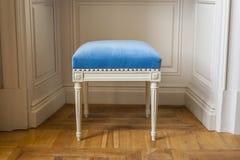 Biała stolec z błękitnym velor tapicerowaniem. Zdjęcie Stock