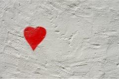 Biała szorstka ściana z małą czerwienią malował serce zdjęcie royalty free