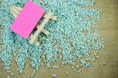 Biała sztaluga z menchiami tapetuje dla inskrypcj na pokruszonym błękitnym żwirze Zdjęcie Stock