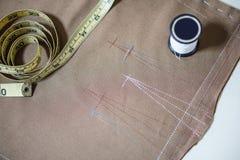 Biała szwalna nić i miękka pomiarowa taśma na tkaniny tkaninie dla robić płótnu Zdjęcie Stock