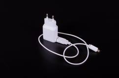 Biała telefon komórkowy ładowarka na czarnym tle Obrazy Stock